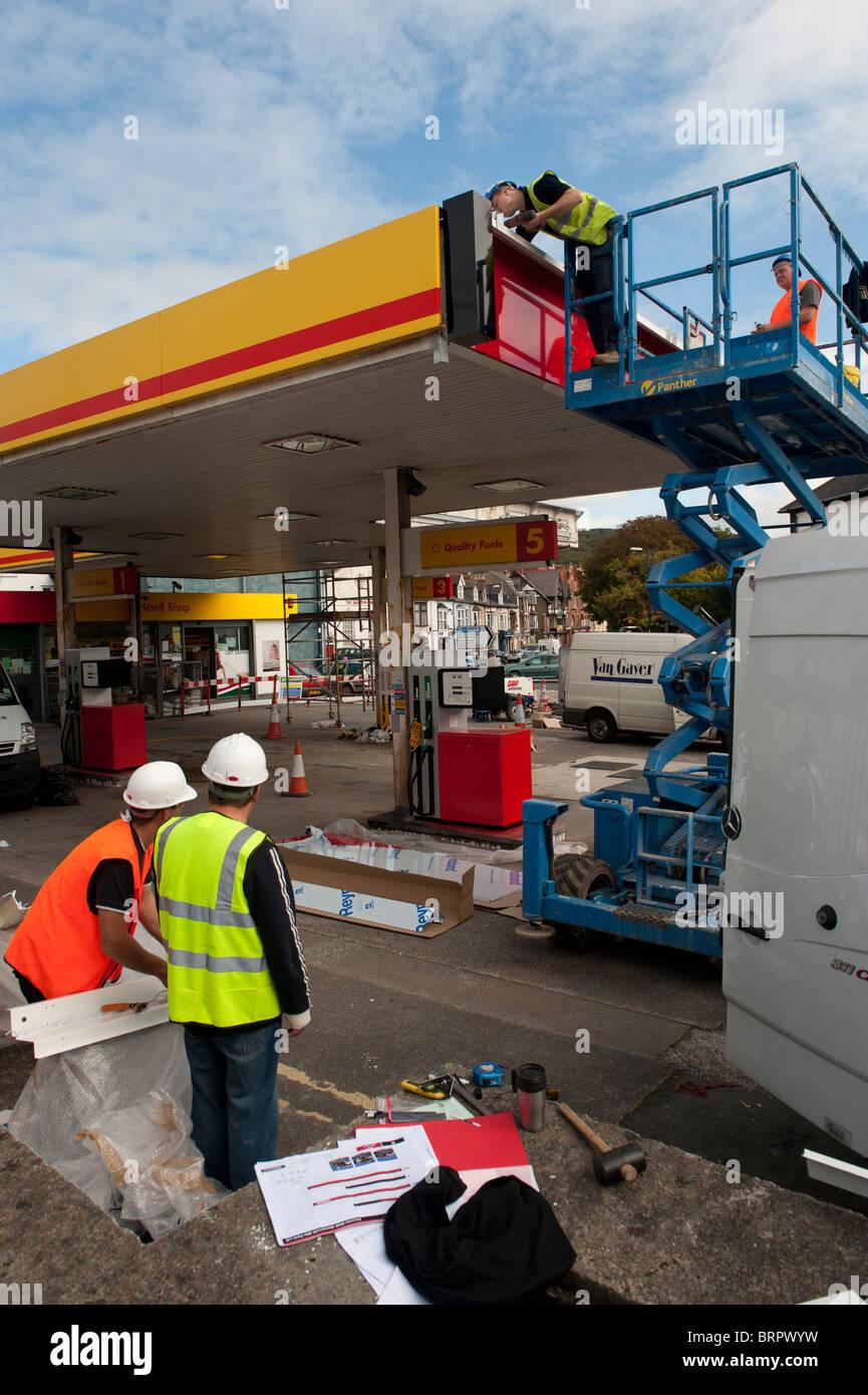 Workmen Renovating and rebranding a Shell petrol station garage as Texaco , UK - Stock Image