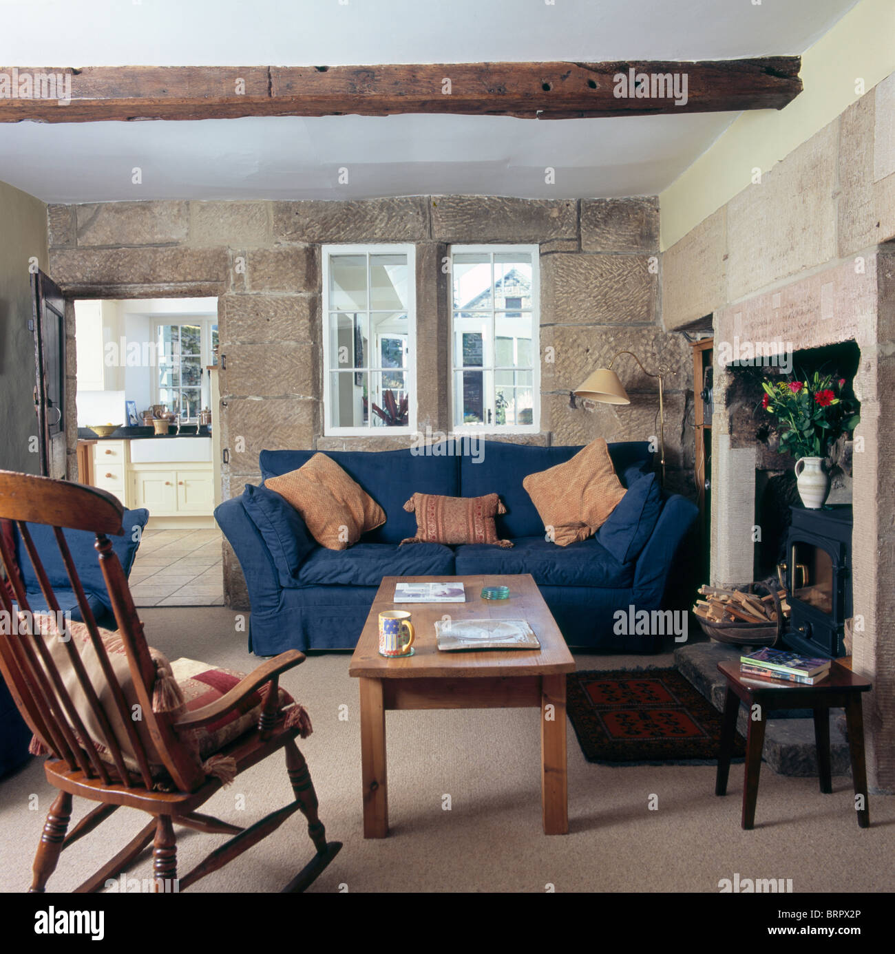 Windsor Chair And Wooden Coffee Table In Cottage Living Room With Blue Sofa  Below Internal Window In Exposed Stone Wall