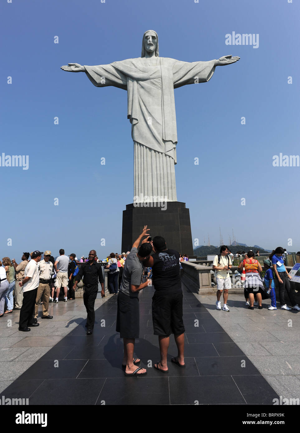 Tourists pose and take pictures in front of the Christ the Redeemer statue on the Corcovado mountain in Rio De Janeiro - Stock Image