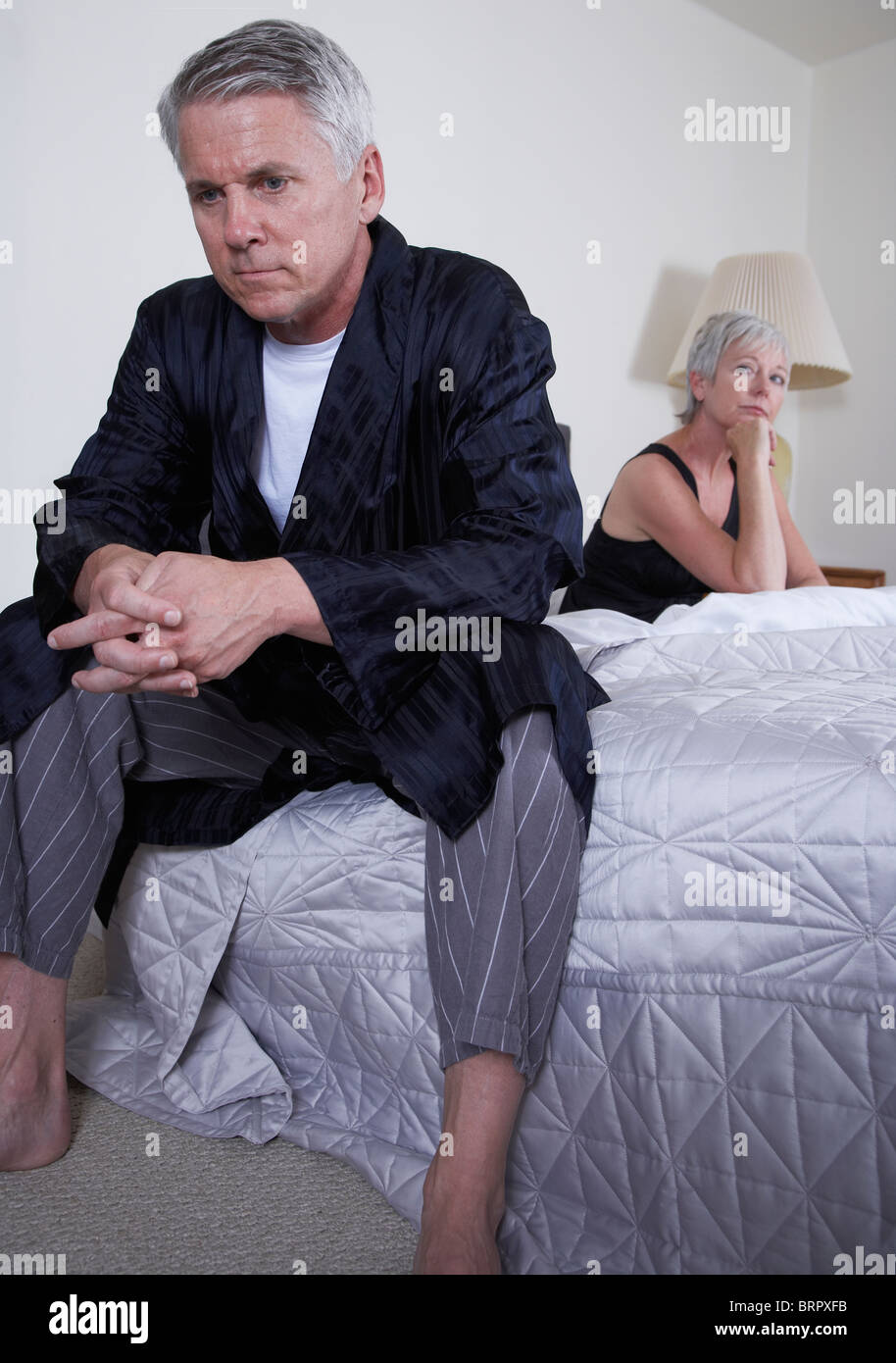 Mature couple sitting apart on bed - Stock Image