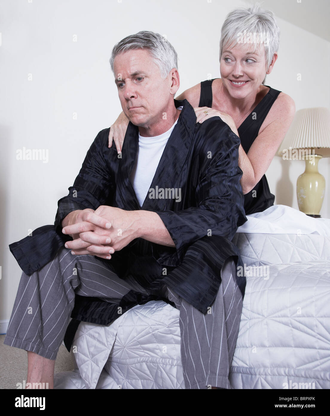 Mature woman consoling man sitting on bed - Stock Image
