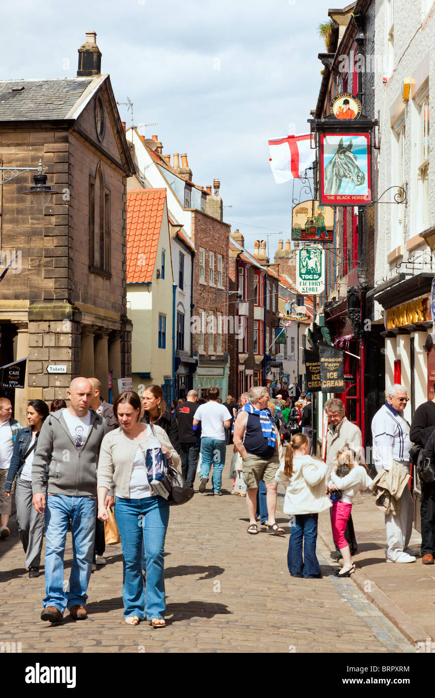 Shoppers in the old streets of Whitby, North Yorkshire, England, UK - Stock Image