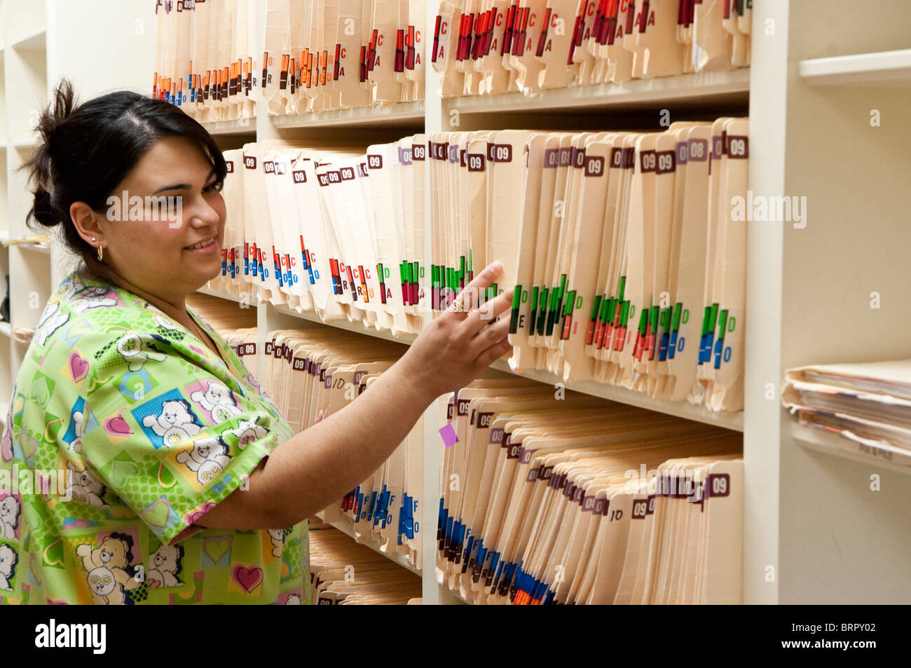 Female medical records clerk at nurse practitioners' office reviews patient medical files in Victoria, Texas. - Stock Image