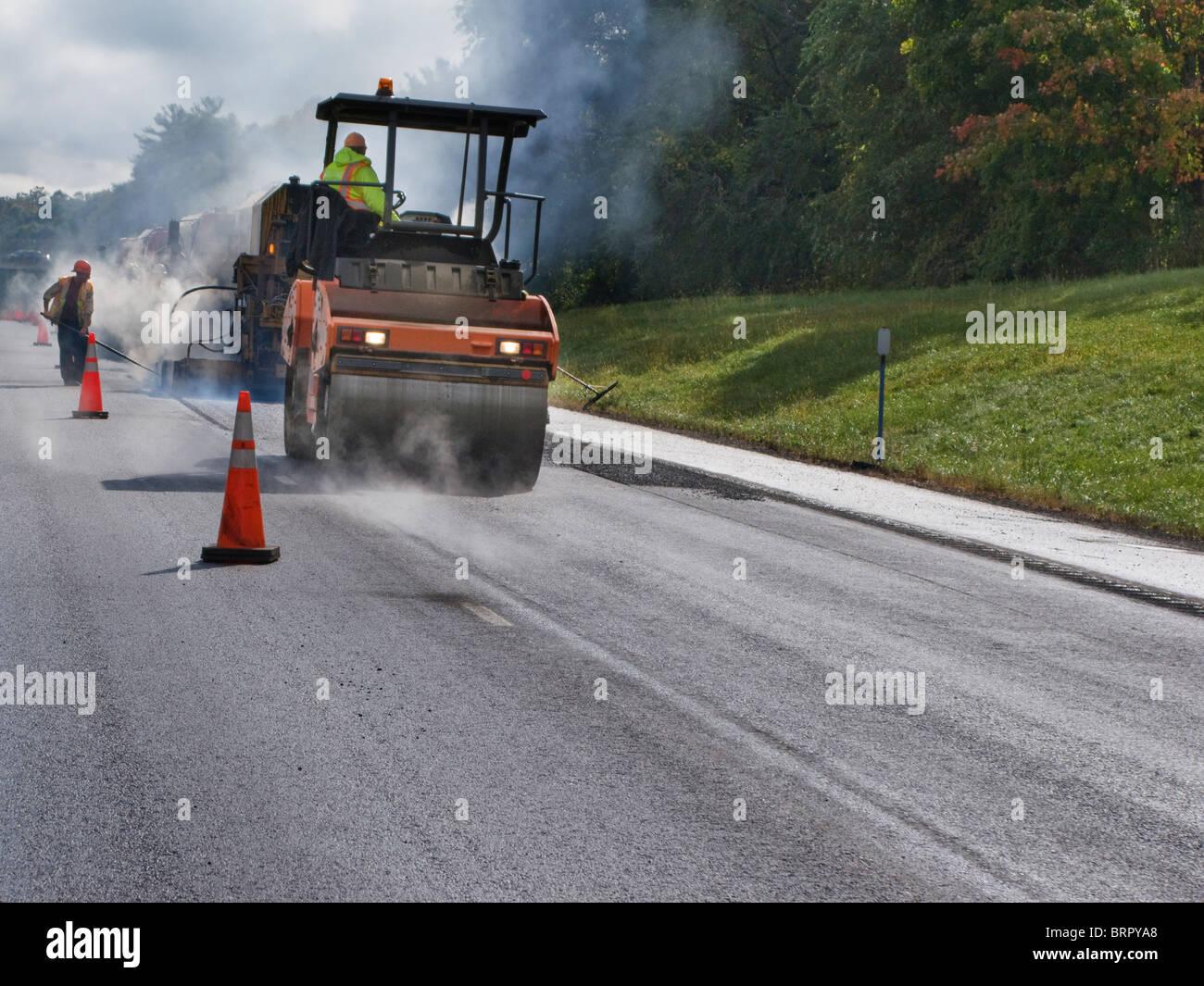 men at work with asphalt paving equipment - Stock Image