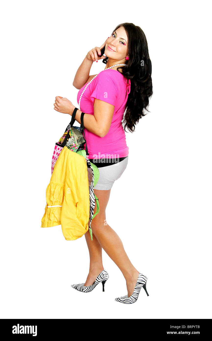 young fashion woman in hot pink and black outfit with shopping purse over white talking on her cell phone - Stock Image
