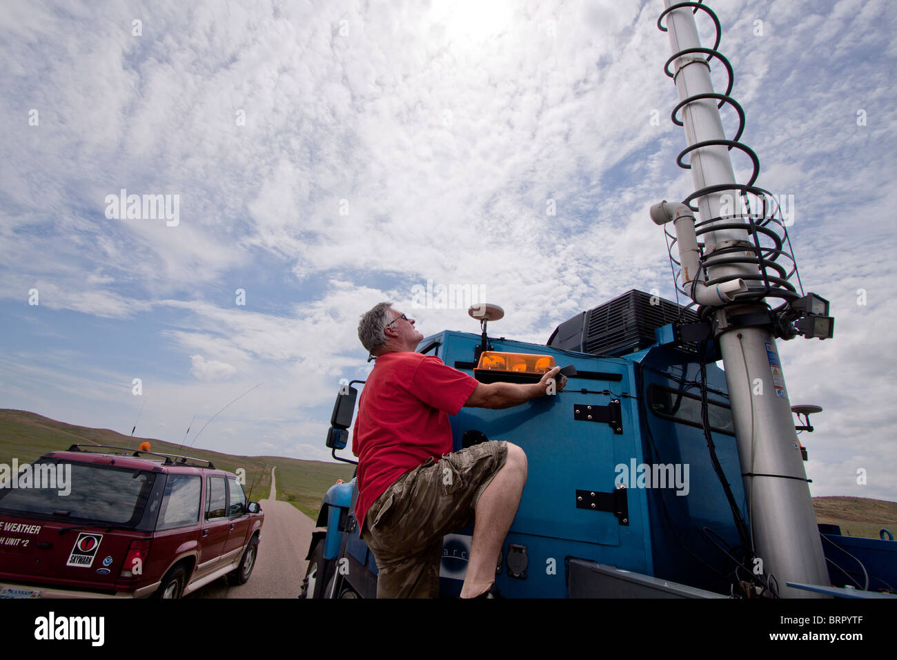 Doppler on Wheels truck number 7 driver Herb Stein climbs atop the truck to tie down the radar dish - Stock Image