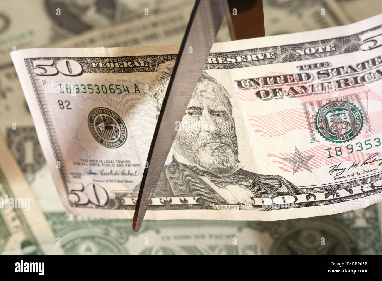 pile of us dollar banknotes with a fifty dollar bill being cut with a pair of scissors - Stock Image