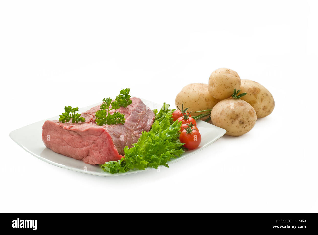 Fresh beef join with potatoes tomatoes salad and herbs - Stock Image