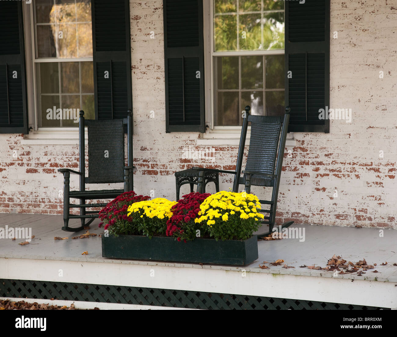 Pair of old rocking chairs on porch of old building in fall Stock Photo