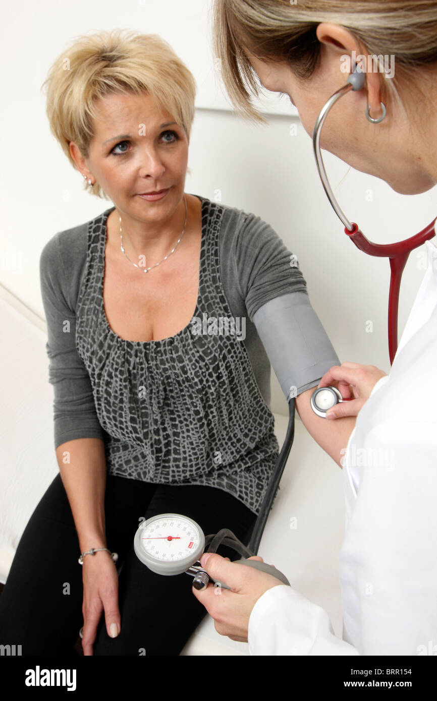 Medical practice, taking the blood pressure of a patient. - Stock Image
