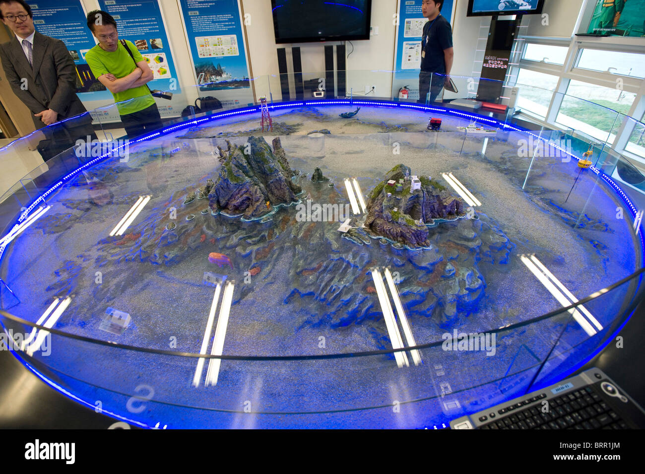 Officials look at a model of the disputed Dokdo Islands, known in Japan as Takeshima, at the East Sea Research Inst., - Stock Image