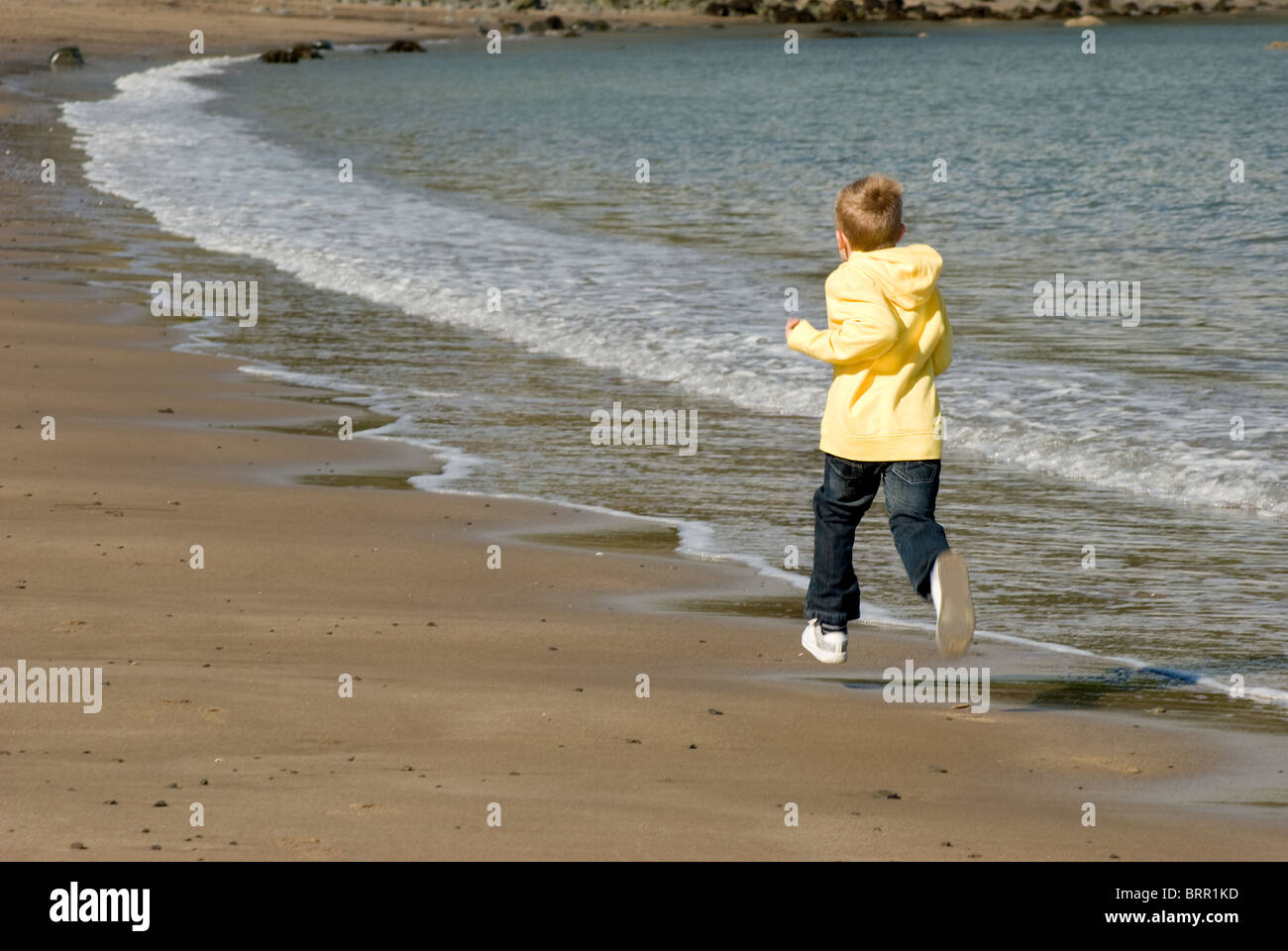 Boy running on the beach at Newquay, West Wales. - Stock Image