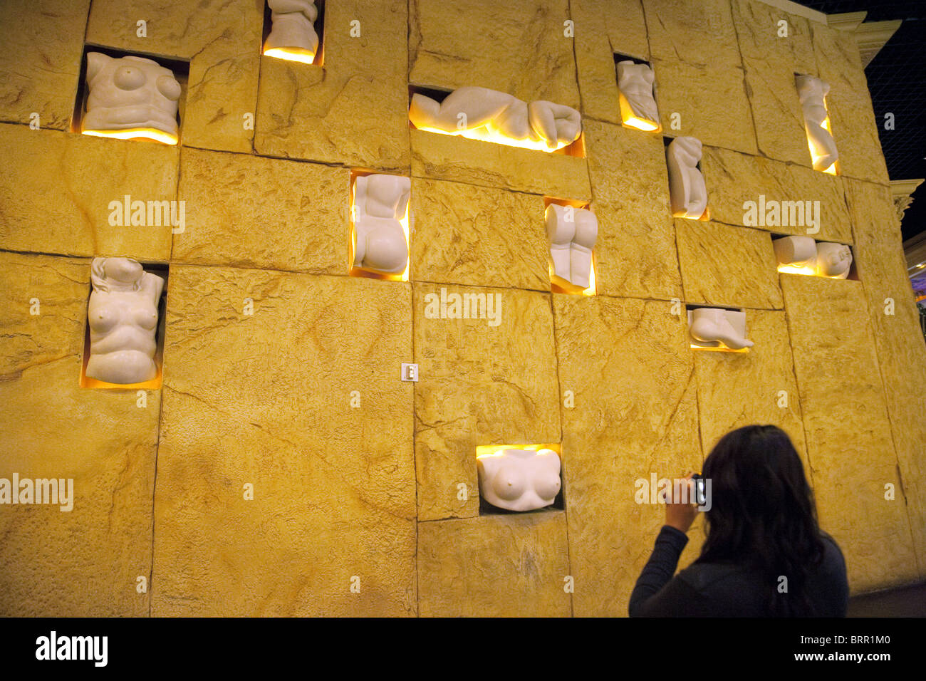A tourist taking a photo of the wall of body parts, the Mandalay Bay Hotel, the Strip, Las Vegas USA - Stock Image