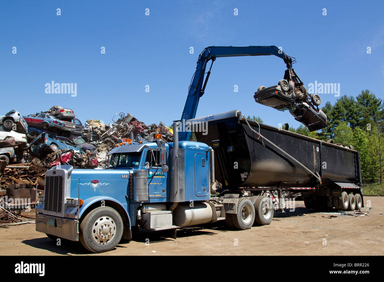Crane loading semi truck with crushed cars, scrap metal automobiles ...