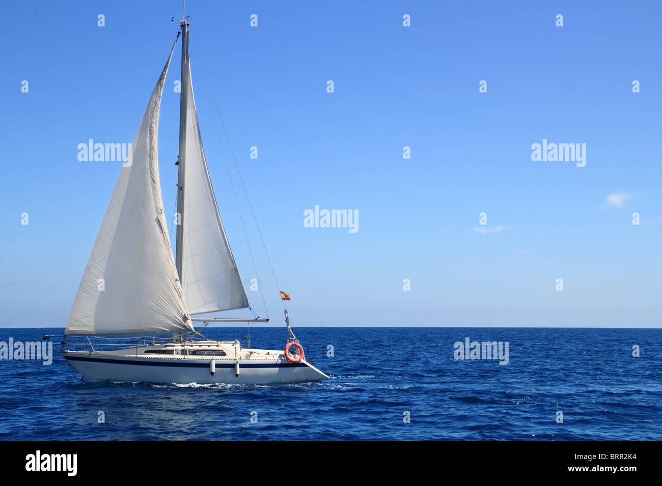 beautiful sailboat sailing sail blue Mediterranean sea ocean horizon - Stock Image