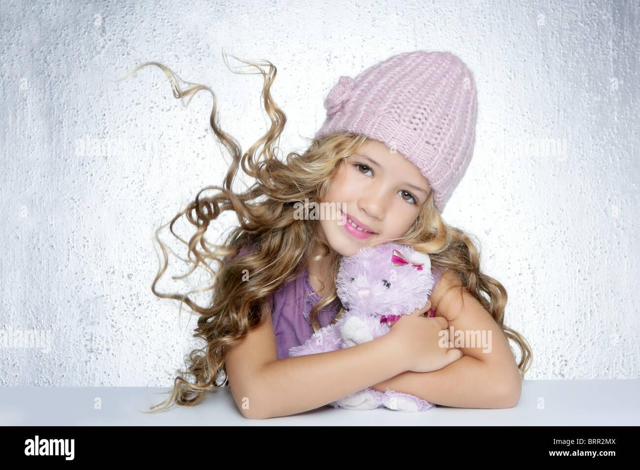 winter fashion cap little girl hug teddy bear smiling silver background -  Stock Image fe562eae0b87