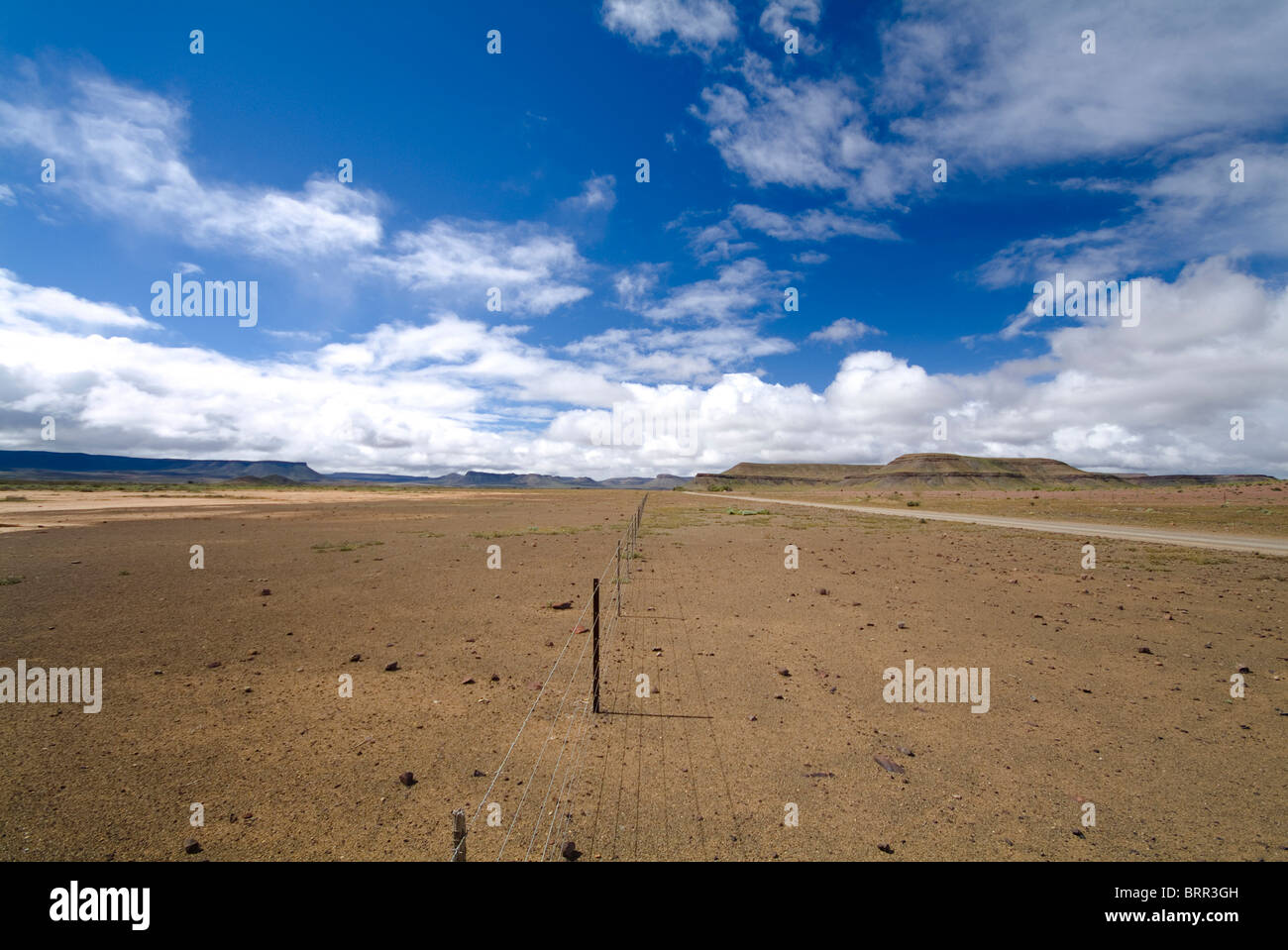 Fence line in a flat arid environment stretching into the distance - Stock Image