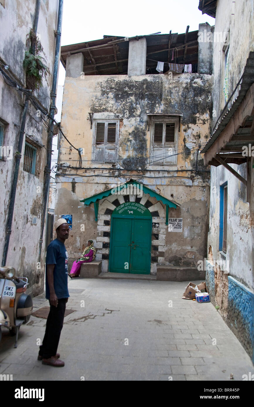 Local man standing in a Stonetown street showing dilapidated buildings - Stock Image