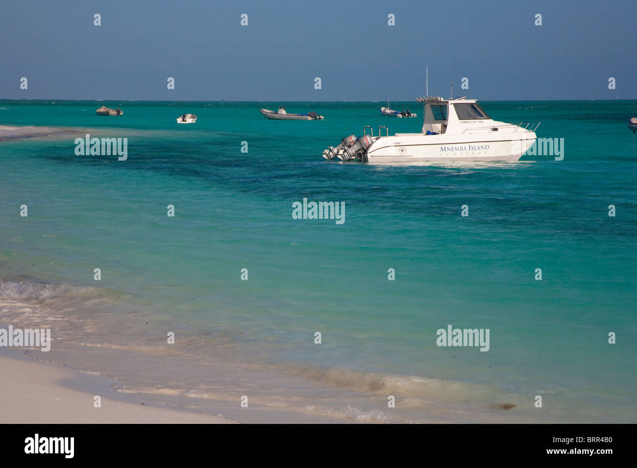 Fishing boat with two outboard motors moored in shallow water off Mnemba island - Stock Image