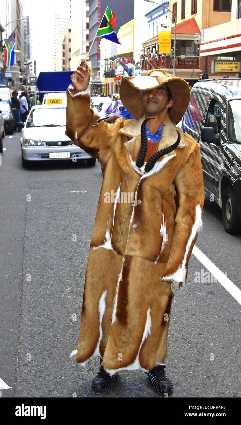 Rugby supporter wearing springbok hide suit and waving South African at a street parade following World Cup win - Stock Image