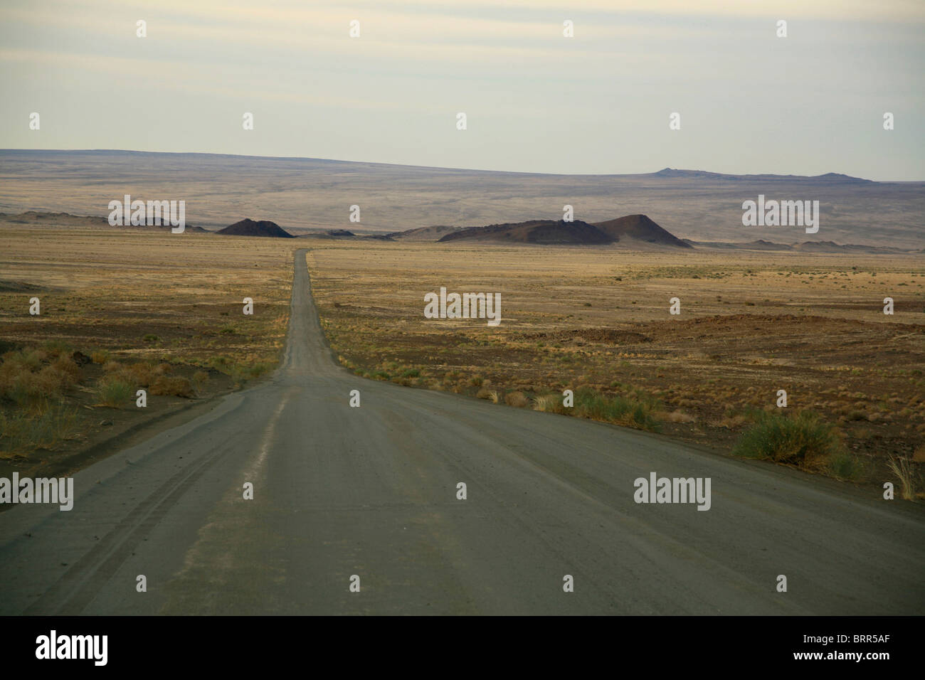 A dirt road running through a remote area stretches into the distance - Stock Image