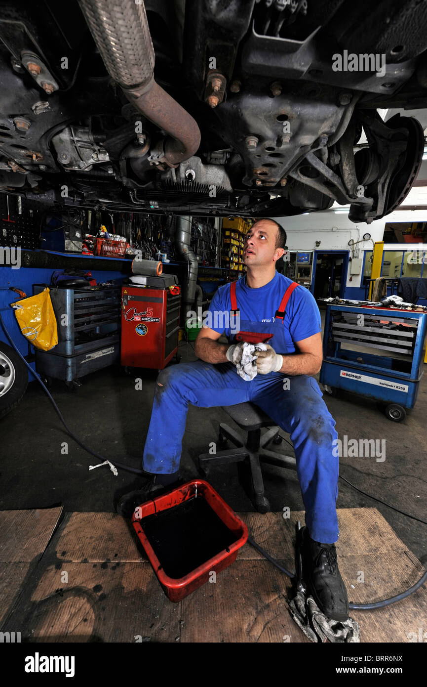 Car workshop with mechanic at work. - Stock Image