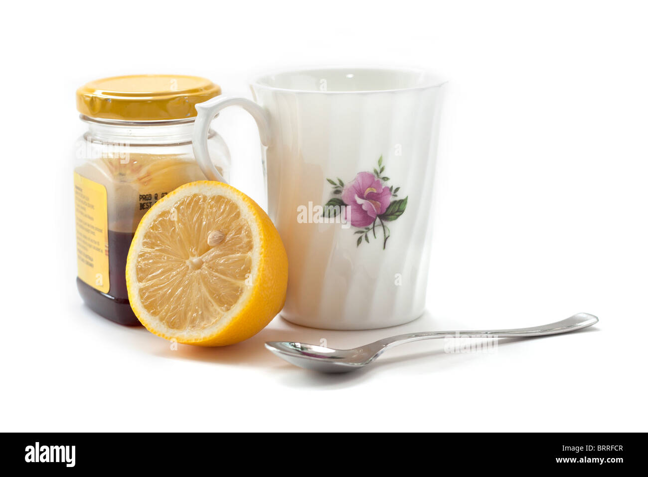 Lemon and honey with mug and spoon for a soothing winter drink in cold and flu season - Stock Image