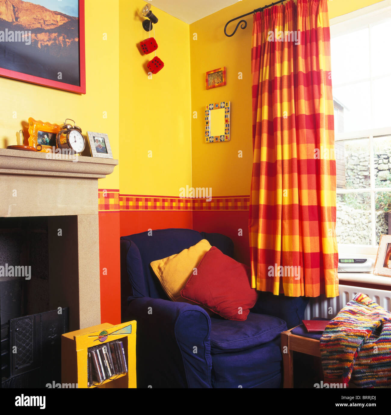 Blue armchair in corner of bright yellow living room with red+yellow ...