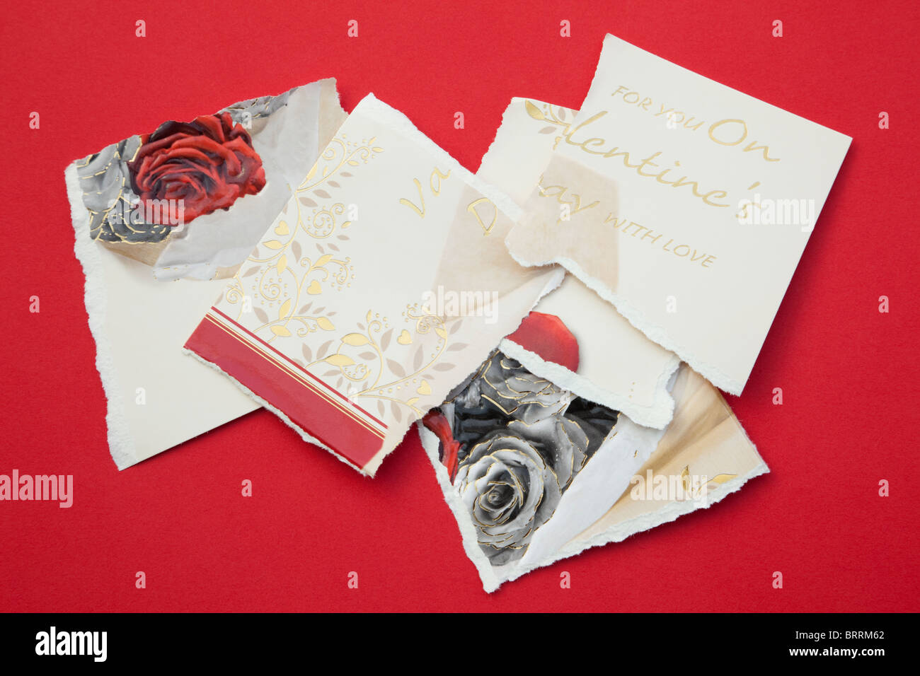 Torn pieces of a Valentine card on a red background - Stock Image