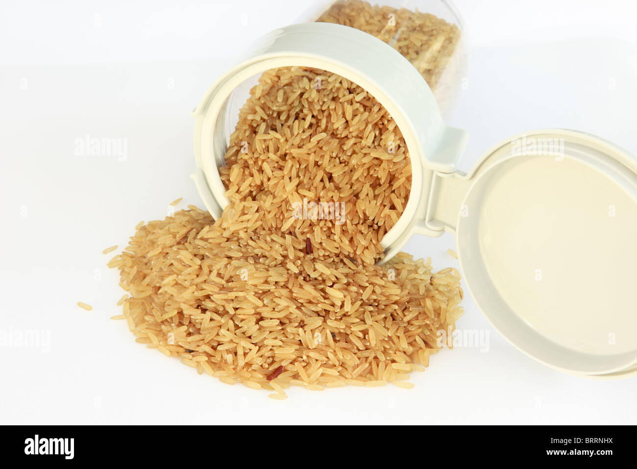 Pile of uncooked brown rice spilling out of a plastic food pot with an open lid top - Stock Image