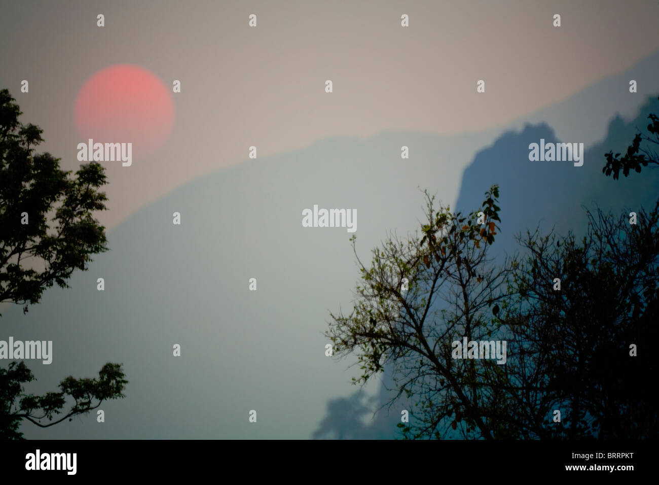 Sun setting through the thick atmosphere among the mountains of Laos. - Stock Image