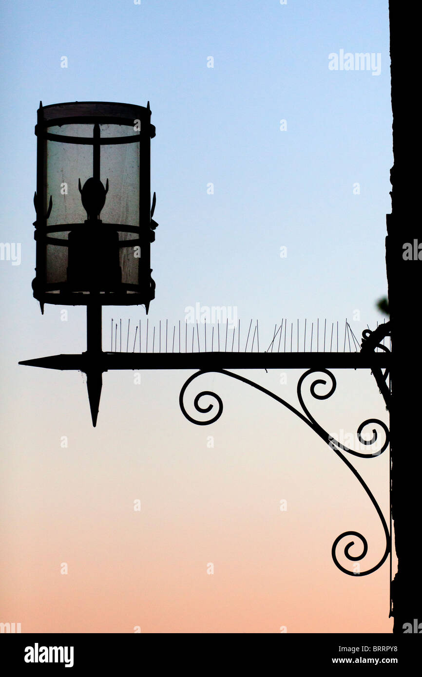 A silhouette of an old fashioned street lamp at dusk - Stock Image