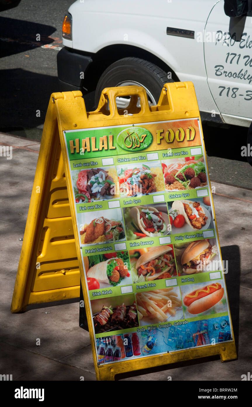 A sign advertises Halal food is served at a vendor's cart in Midtown in New York - Stock Image