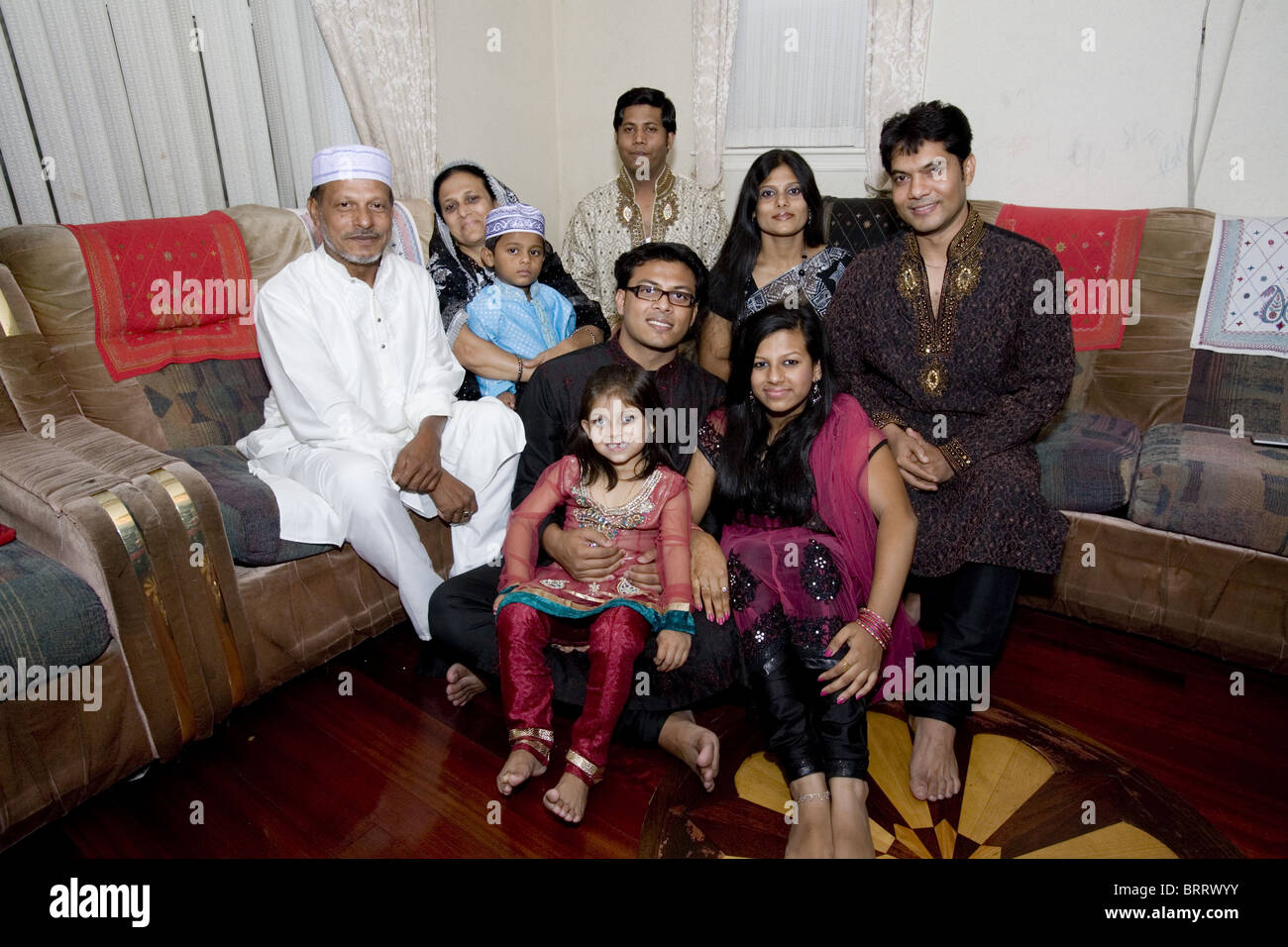 Three generation Bangladeshi American Muslim family gets together at the end of Ramadan on Eid to break the fast - Stock Image