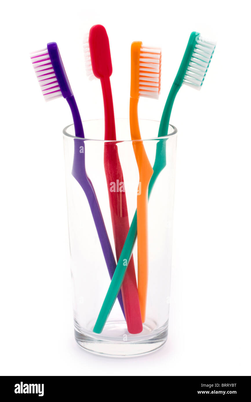 colourful toothbrushes in a glass over white - Stock Image