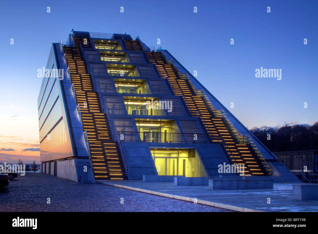 Modern Dockland office building on Elbe River at sunset, stairs leading to the roof on the backside, fishing harbour - Stock Image
