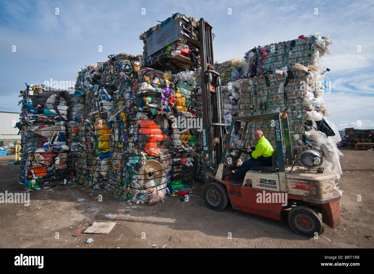 Stacking one tonne bales of plastic with a forklift at a plastics recycling plant in Geelong Australia - Stock Image