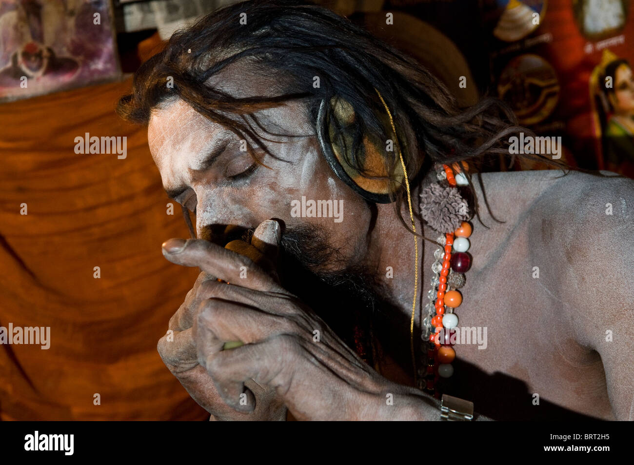A Naga Sadhu smoking his chillum. - Stock Image