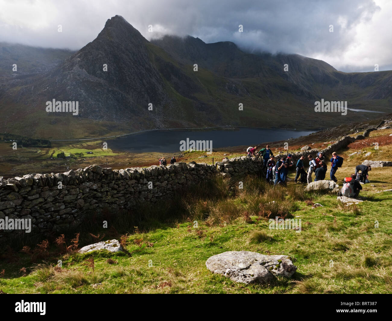 Snowdonia: Tryfan and the Glyders rise over Llyn Ogwen, while a group of walkers rest on the flanks of Pen yr Ole - Stock Image