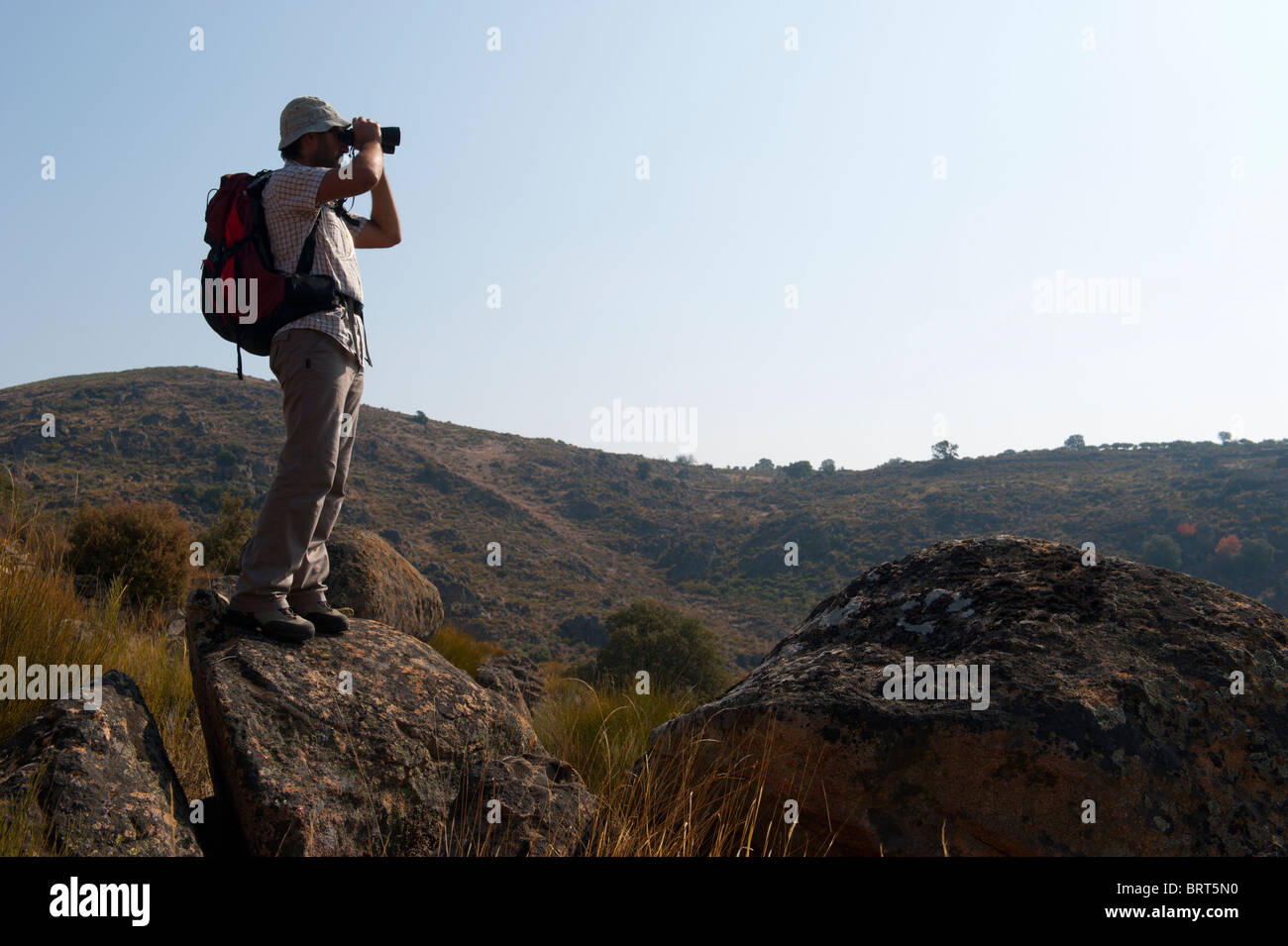 Young man with backpack looking through binoculars on top of a rock against the sky Stock Photo