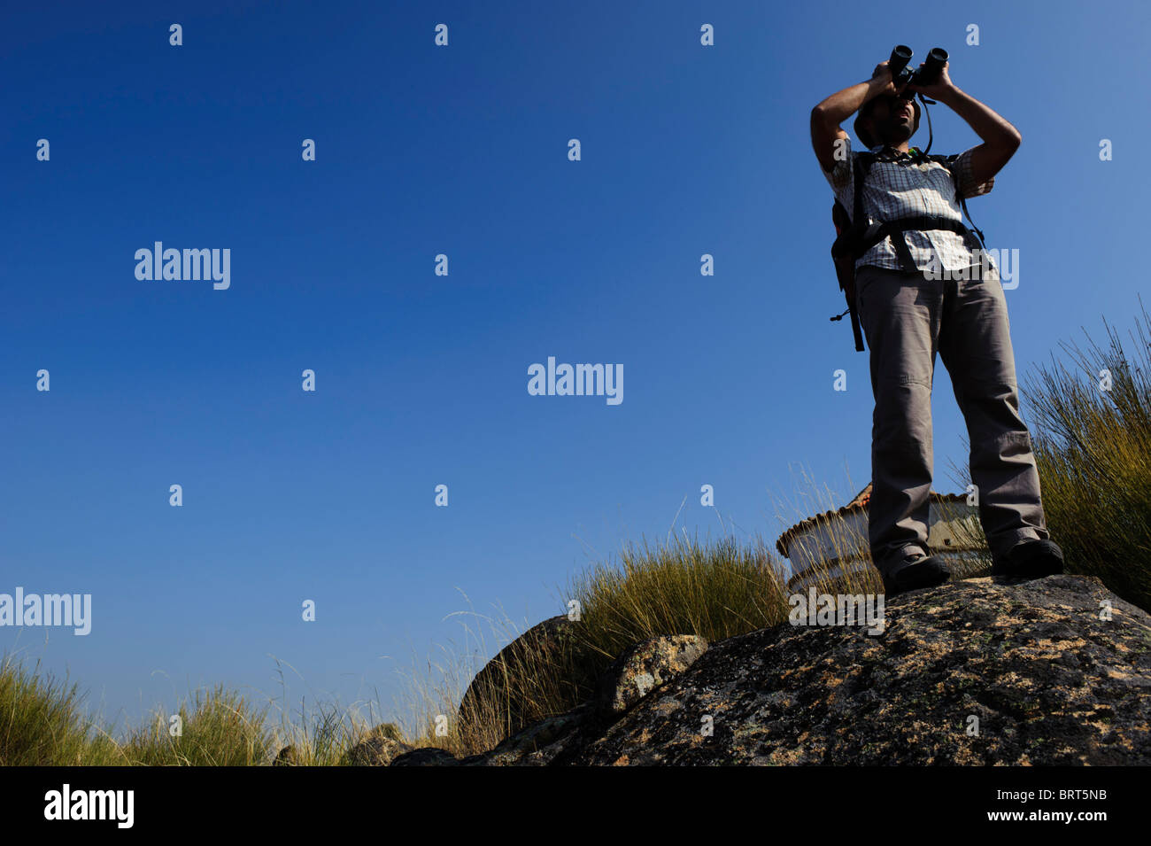 Young man with backpack looking through binoculars on top of a rock against the sky - Stock Image