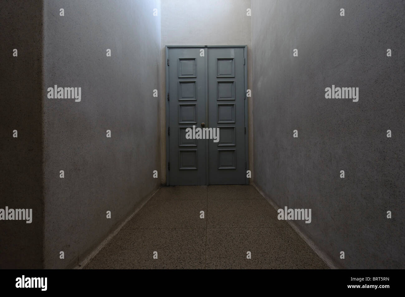 Closed door at the end of a dark corridor - Stock Image