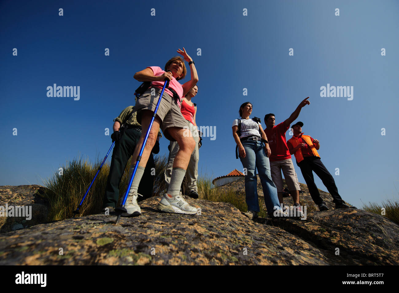 Group of hikers bird watching on top of a rock - Stock Image