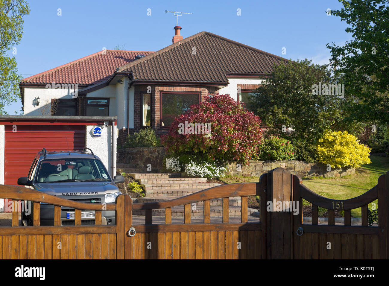Bungalow front garden, gates and drive with car parked, Wirral, Merseyside, England - Stock Image