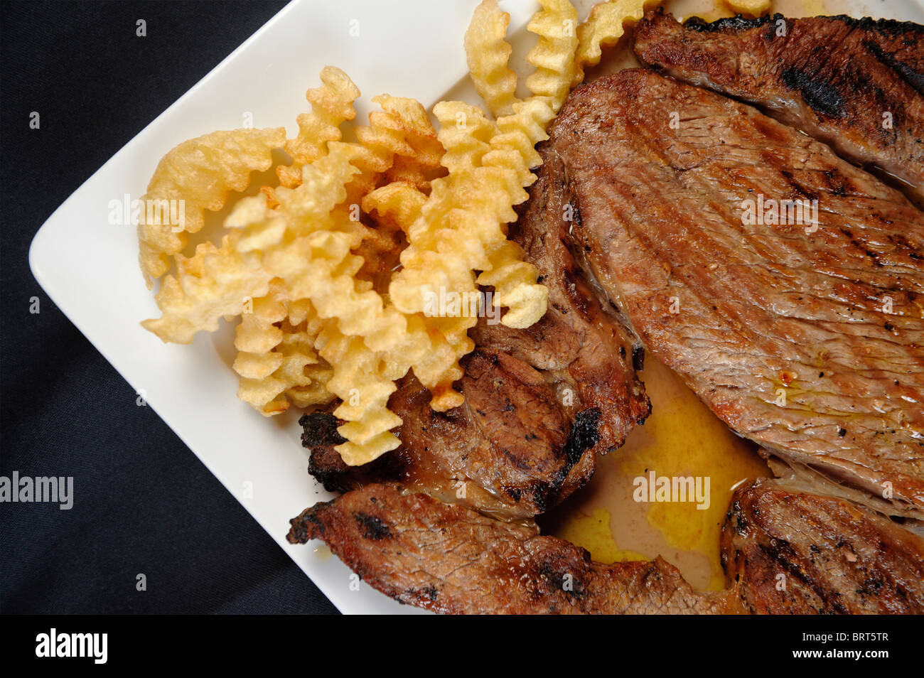 Detail shot of grilled steak with french fries - Stock Image