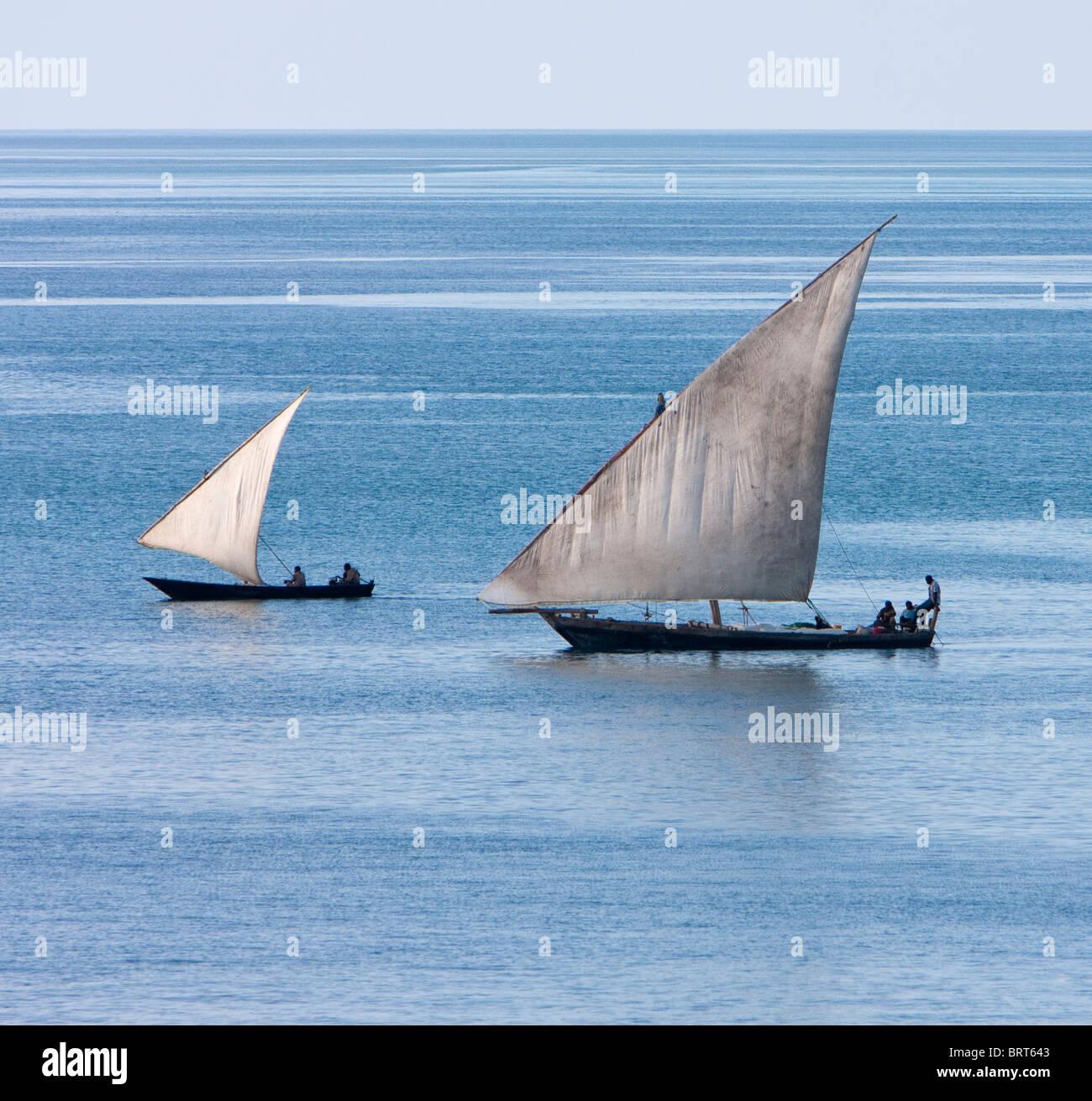 Zanzibar, Tanzania. Lateen Sail on Dhow and Canoe in Harbor. - Stock Image