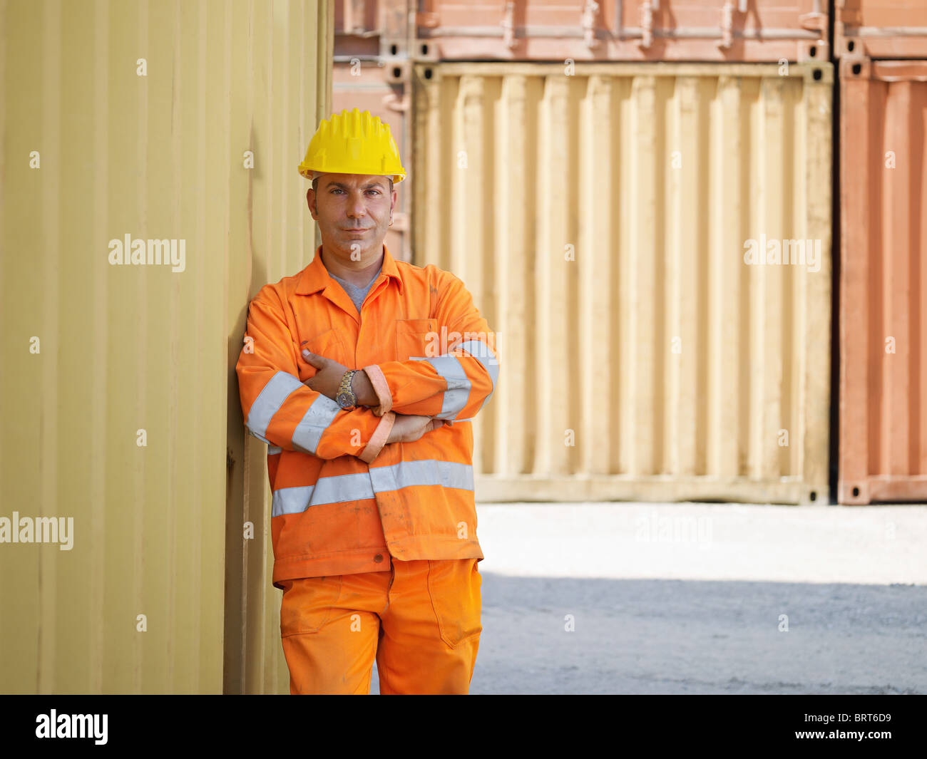 portrait of mid adult worker standing near cargo containers and looking at camera. Horizontal shape, front view, - Stock Image