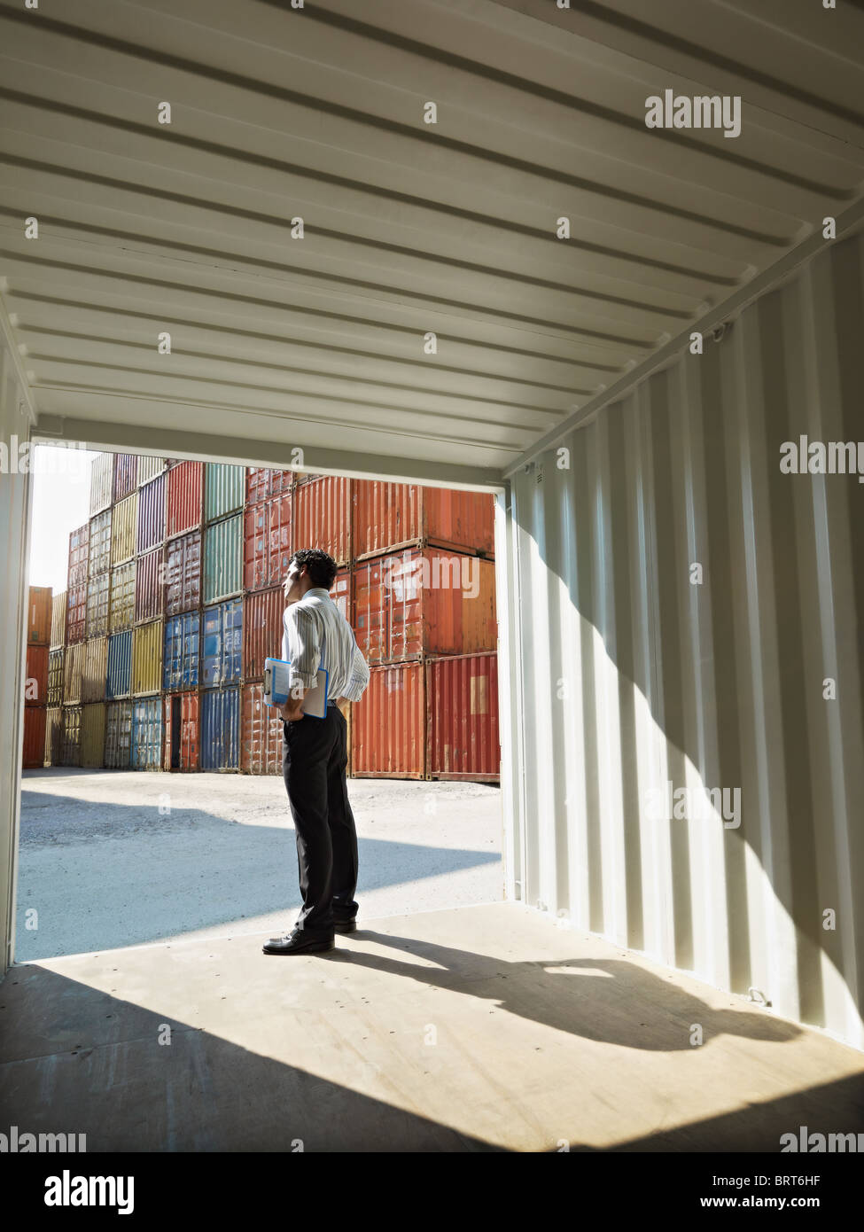 portrait of mid adult businessman standing near cargo container. Vertical shape, side view, copy space - Stock Image