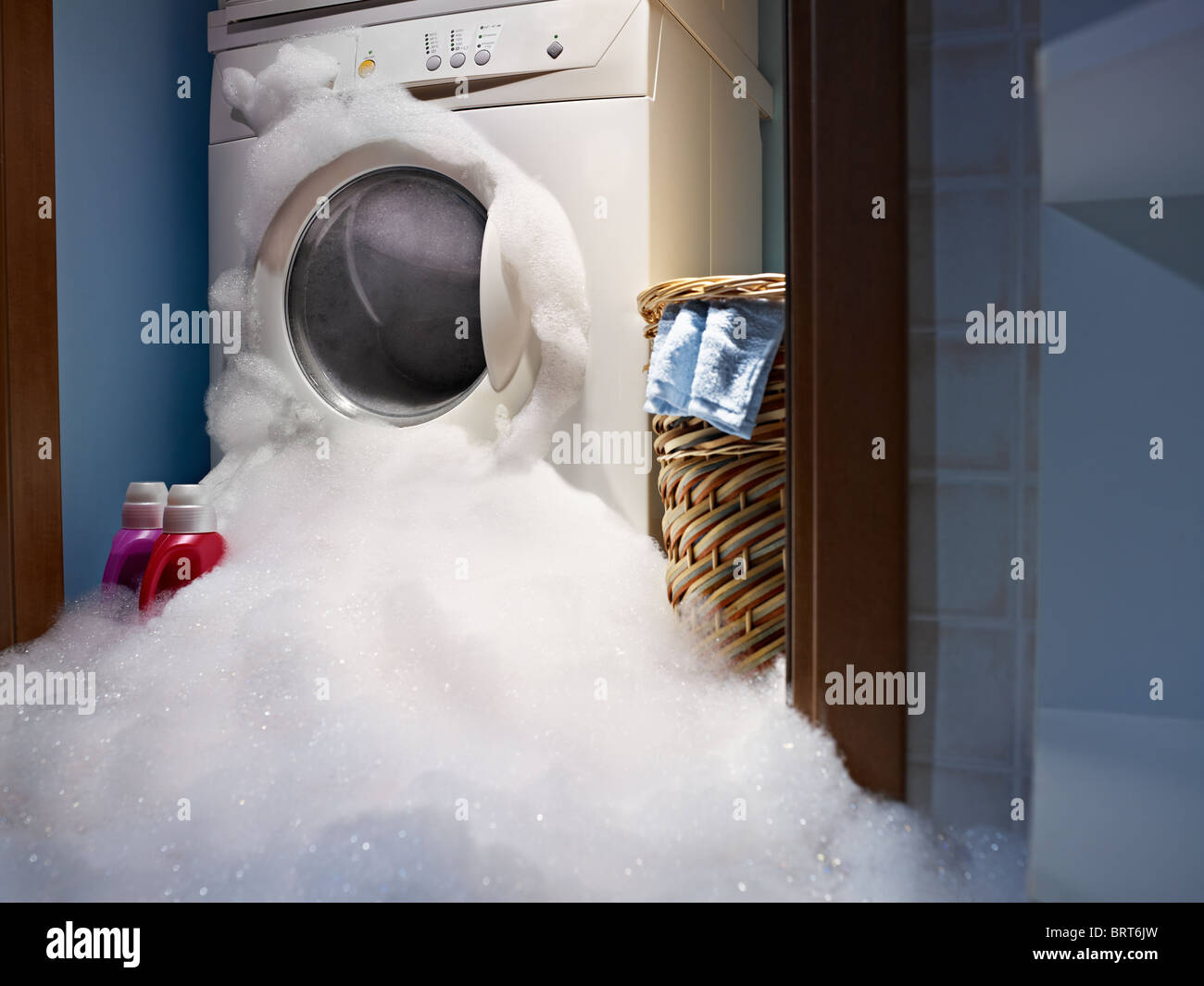 soap coming out from broken washing machine. - Stock Image