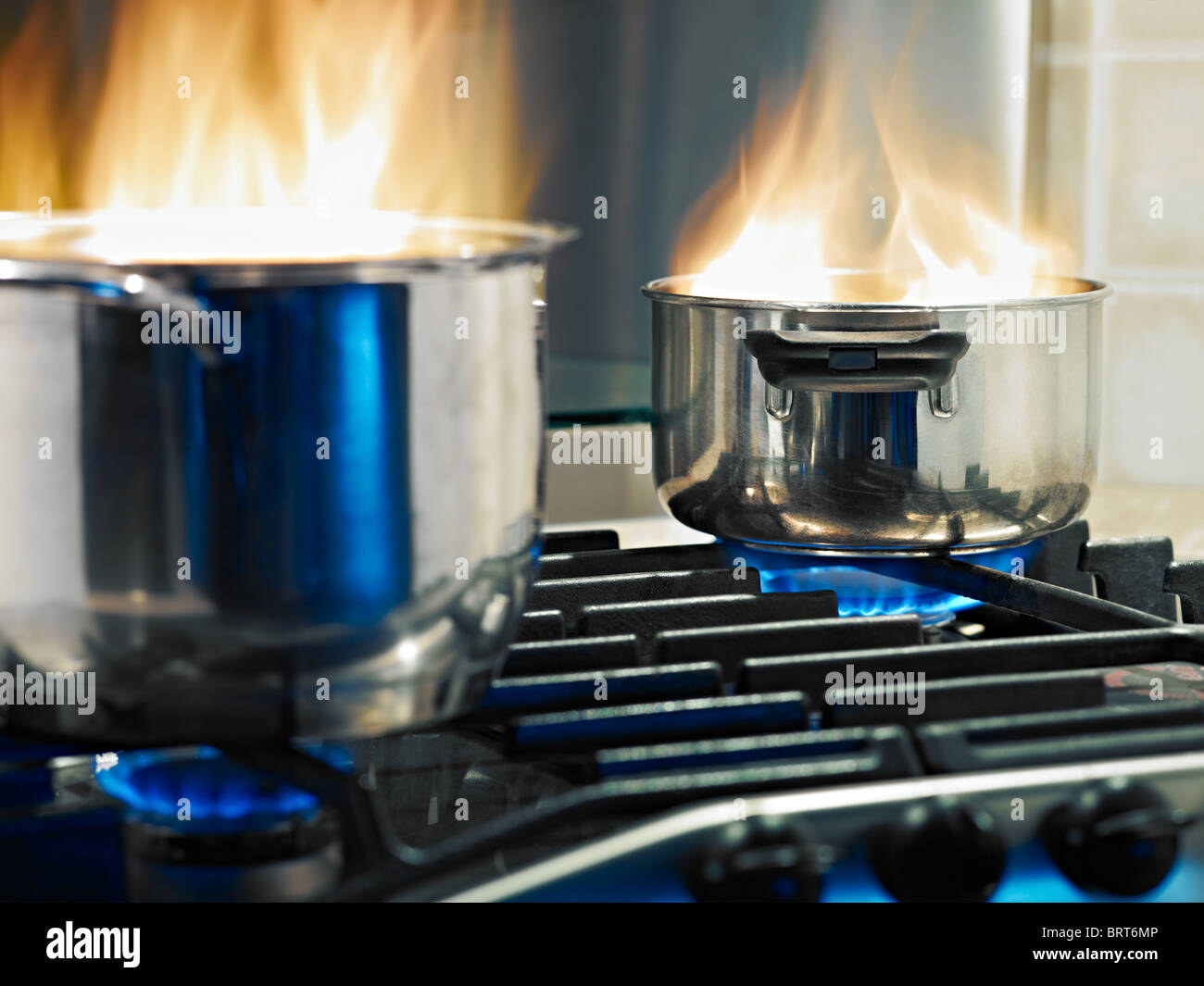 pans in fire on stoves. Horizontal shape - Stock Image
